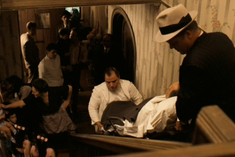 Two attendants carry Marlon Brando in The Godfather
