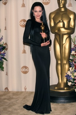Actress Angelina Jolie, wearing black gown and holding her Oscar, in Press Room at Academy Awards, March 26, 2002.