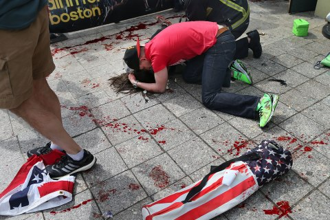 A man comforts a woman on the sidewalk at the scene of the first explosion near the finish line of the 117th Boston Marathon, April 15, 2013.