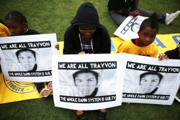 A group of children hold signs with Trayvon Martin pictured on them in Phoenix, on July 16, 2013.