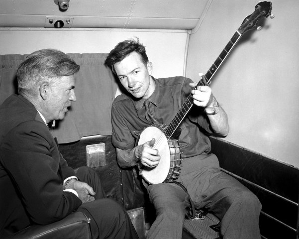 From left: Henry A. Wallace, making a political tour of the American South, listens to Pete Seeger play the banjo on a plane between Norfolk and Richmond, Aug. 28, 1948.